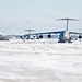 U.S. Airmen tow a C-5M Super Galaxy aircraft at Dover Air Force Base, Del., Jan. 3, 2014. Airmen with the 436th Civil Engineer Squadron cleared snow from the flight line after a storm. (U.S. Air Force photo by Roland Balik/Released)