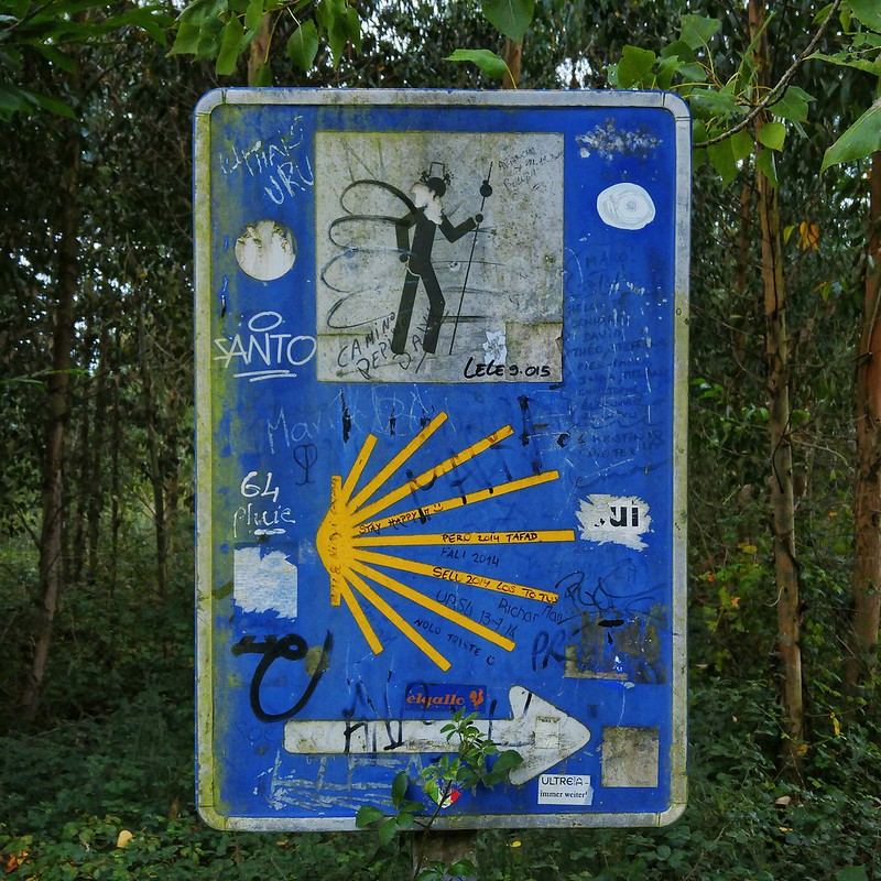 A graffitied Camino walking sign