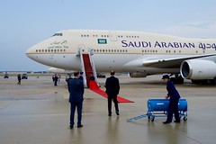 U.S. Chief of Protocol Ambassador Peter Selfridge watches as a red carpet is rolled out before a Boeing 747 carrying King Salman bin Abdulaziz of Saudi Arabia after it arrived at Andrews Air Force Base in Camp Springs, Maryland, on September 3, 2015, so the King could visit President Barack Obama.  [State Department photo/ Public Domain]