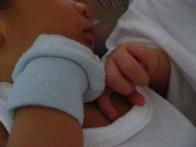 Baby wearing a mitten.