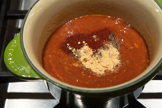 adding spices to bbq sauce pot