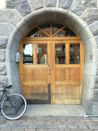 rounded stone doorframe with wooden door and bike Copenhagen