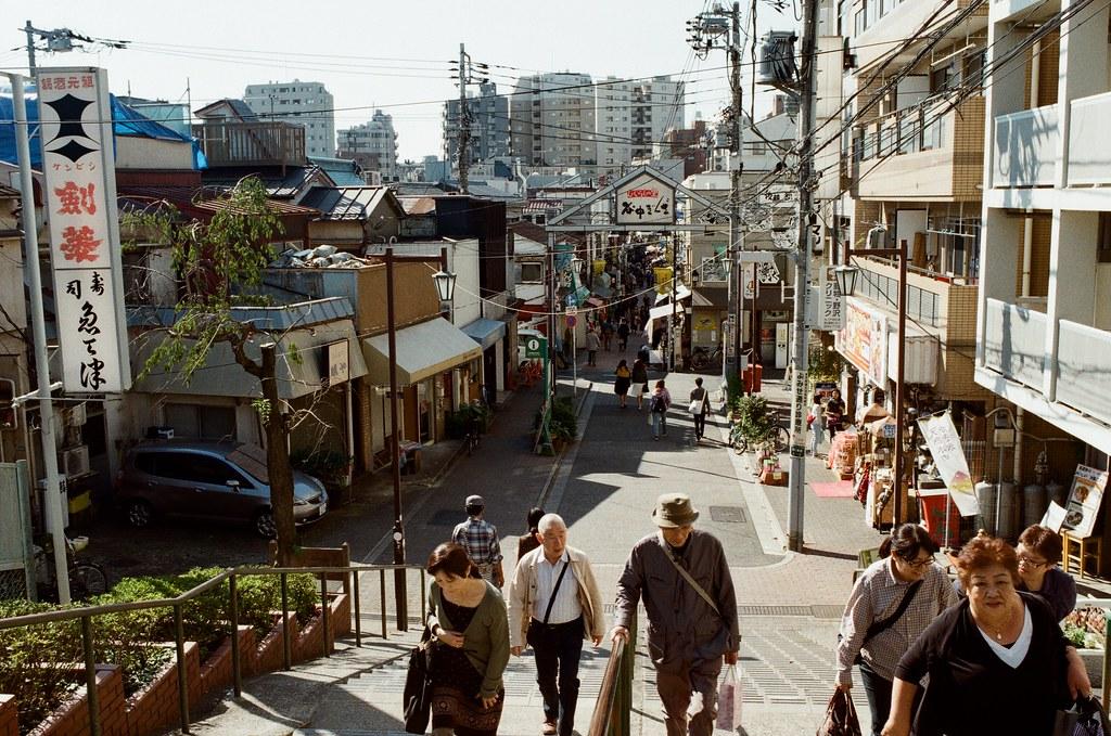 谷中銀座 日暮里 東京 Tokyo 2015/10/08 離開在東京荒川住的地方準備去成田機場回台灣,沿途經過日暮里,就到旁邊的谷中銀座走走。  應該不需要說,這裡來過,我只是想把這段記憶再走一遍。  我從與當初相反的方向走,回憶就剛好用倒轉的方式進行。  最後找到一間民宅,不小心被妳發現我在注意妳的腳步。  Nikon FM2 Kodak ColorPlus ISO200 Nikon AI AF Nikkor 35mm F/2D 1003-0023 Photo by Toomore