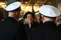 Japanese Prime Minister Shinzo Abe, center, listens as Capt. Christopher Bolt, left, commanding officer of USS Ronald Reagan (CVN 76), and Rear Adm. John Alexander, commander of Battle Force 7th Fleet, explain shipboard operations. (U.S. Navy/MC1 Chris Henry)