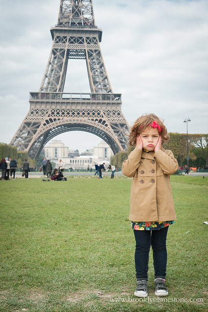 Aggie with her hands on her cheeks and a pout face at the base of the Eiffel Tower
