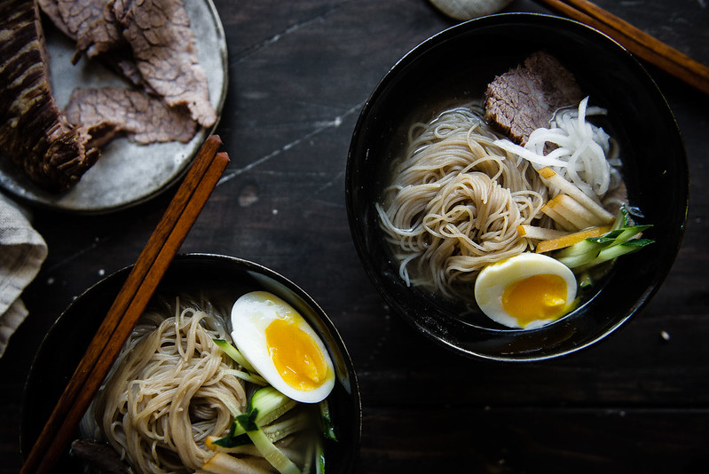 mul naengmyeon (korean cold noodle soup) | two red bowls