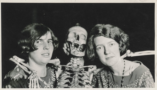 Two women pose with their skeleton friend