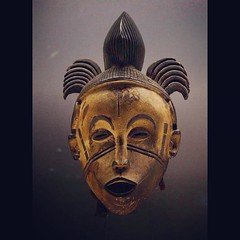 Anthropomorphic mask Igbo or Idoma culture, Nigeria 20th century Wood, textile, pigments. Light colored female face with sculptural details, eyebrows, eyes, ears, scars are outlined in black. The open mouth reveals a row of tightly packed teeth. Scarifi
