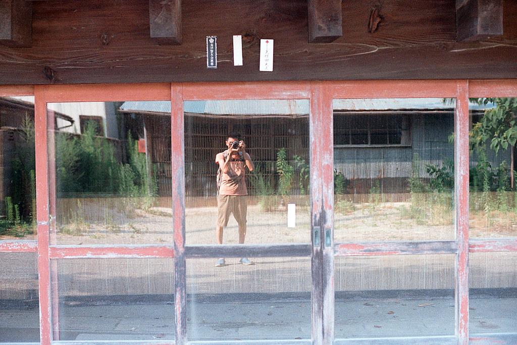 "自己 福島縣雙葉郡楢葉町 2015/08/06 一戶人家的門面,把自己拍進去,那時就是這樣背著包包一路往北。  Nikon FM2 / 50mm Kodak ColorPlus ISO200  <a href=""http://blog.toomore.net/2015/08/blog-post.html"" rel=""noreferrer nofollow"">blog.toomore.net/2015/08/blog-post.html</a> Photo by Toomore"