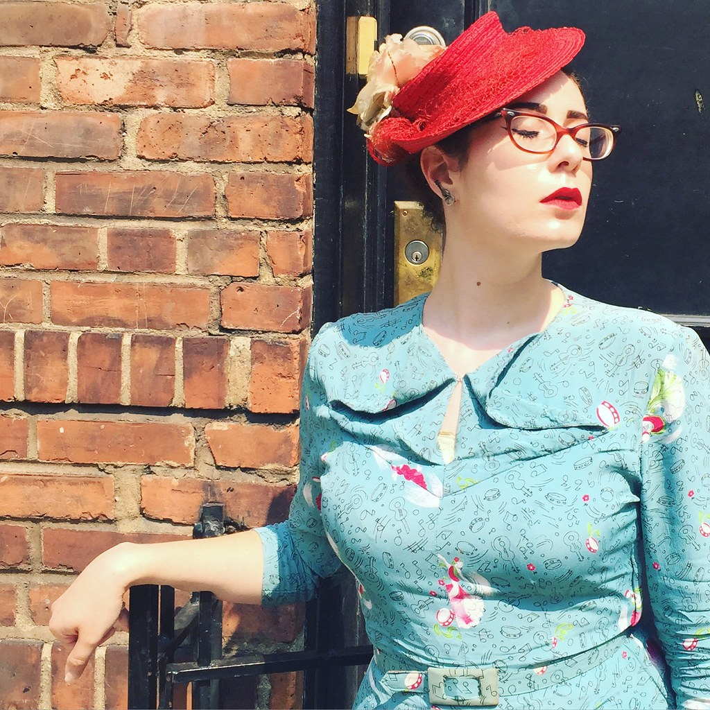 Hannah models a music-themed aqua 1940s novelty print dress with a red straw tilt hat
