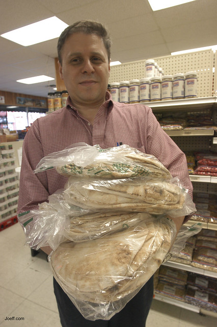 Syrian Maher Dalati loads up on pita bread at Al-Khyan