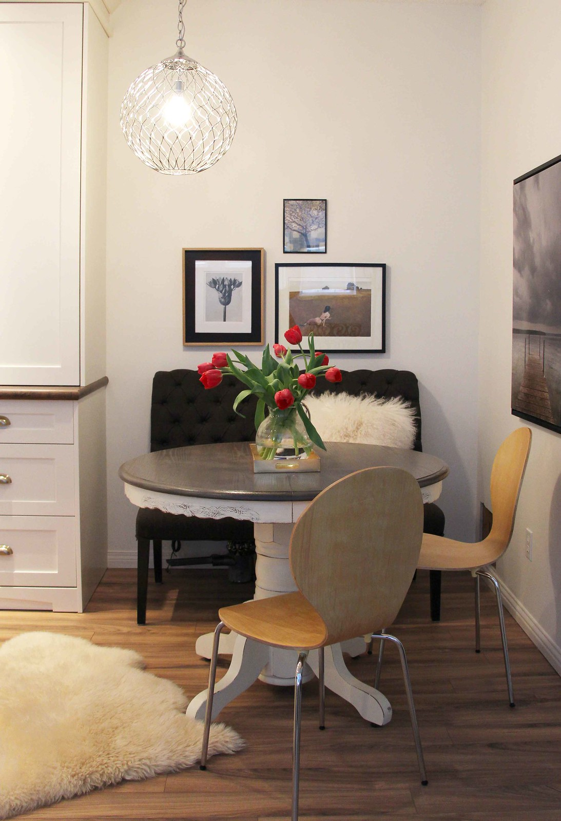 benjamin moore ballet white on walls in this kitchen nook with antique round table and modern chairs
