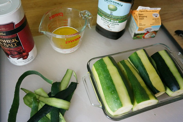 Zucchini nestle in a baking dish, strips of peel tangled on the cutting board beside, while containers of cream, olive oil, and salt sit around the periphery: that's all that's in the dish!