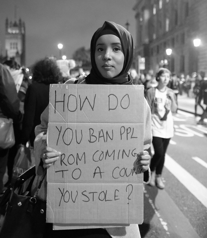 Protester with a message about the irony of Trump's blanket immigration ban.