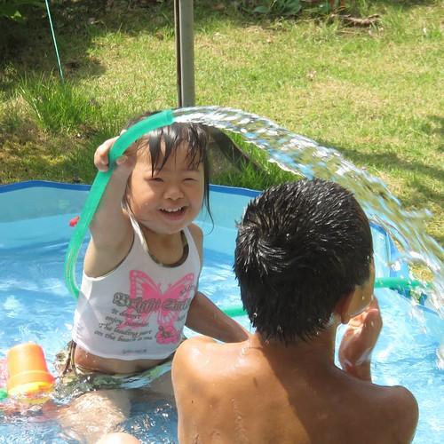 満面の笑みで兄に水かける娘さん