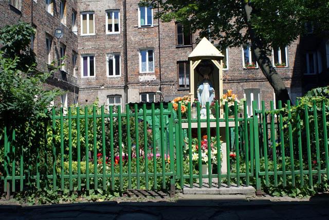 Statue de Marie devant une parterre de fleurs.