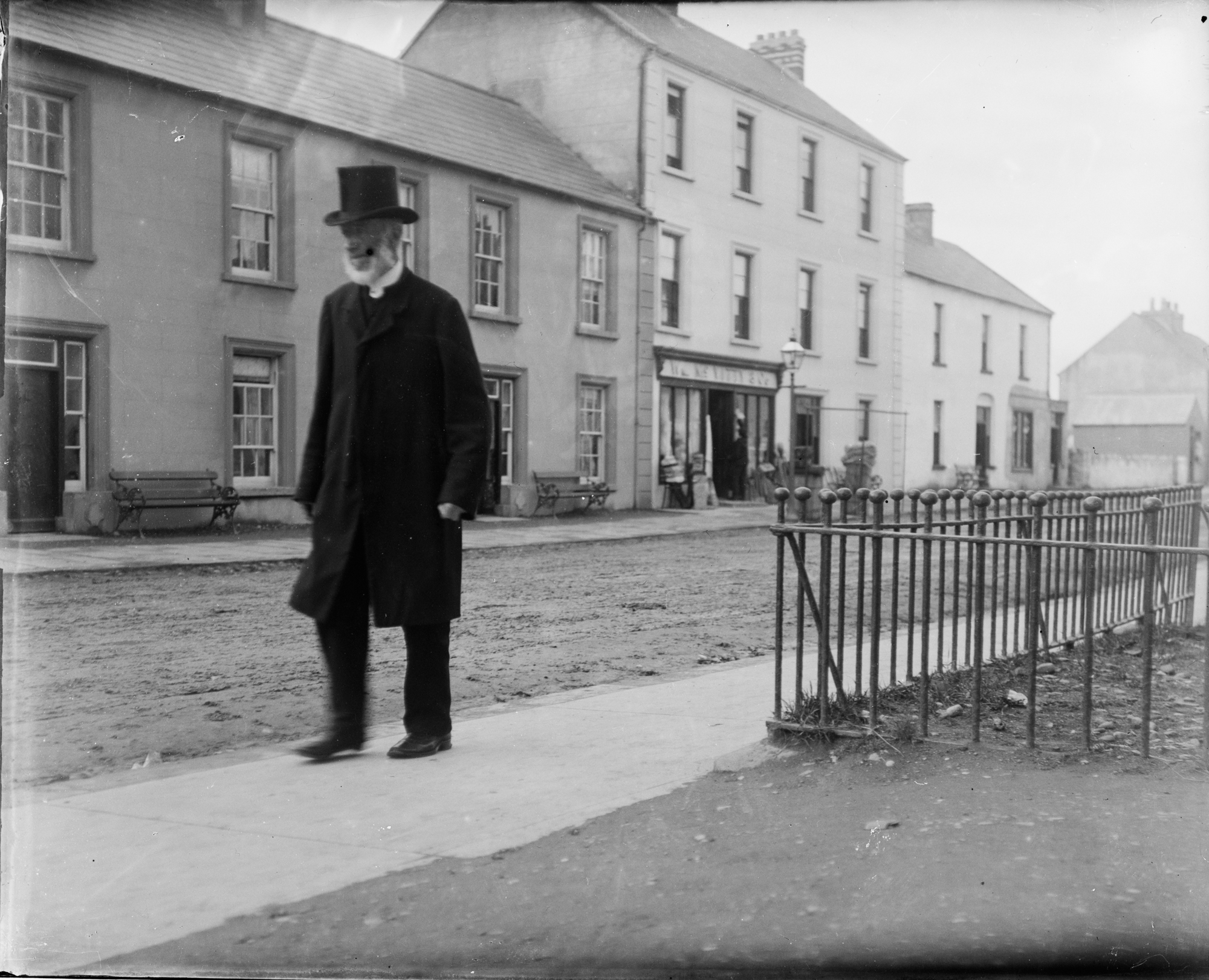 Man with beard and top hat walking along a road (in Bundoran)