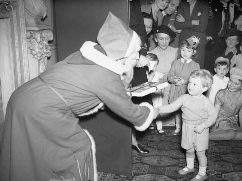Father Christmas presents Winston Churchill Jr., the Prime Minister's grandson, with a gift at a Christmas party at Admiralty House in London, 17 December 1942