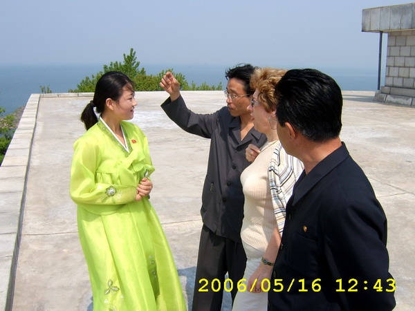 North Korea: tour guide being corrected by a supervising guy