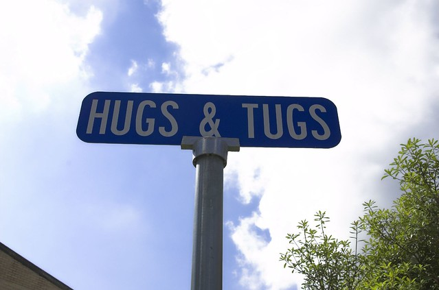 A street sign saying hugs and tugs, probably implying a happy ending