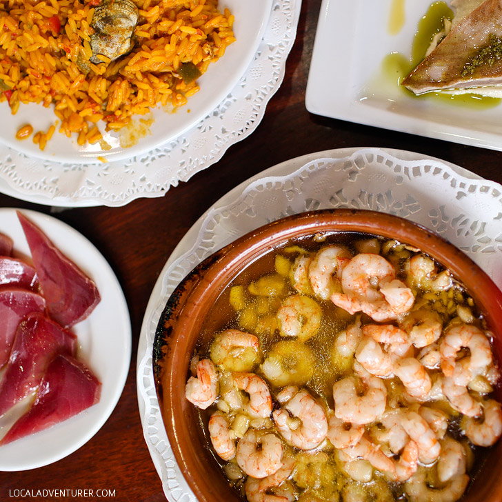 Gambas al Ajillo is a sizzling Spanish dish of seasoned prawns in olive oil. It's a must try if you're in Spain. Click through to see the other 15 Spanish foods you must try when visiting Spain.