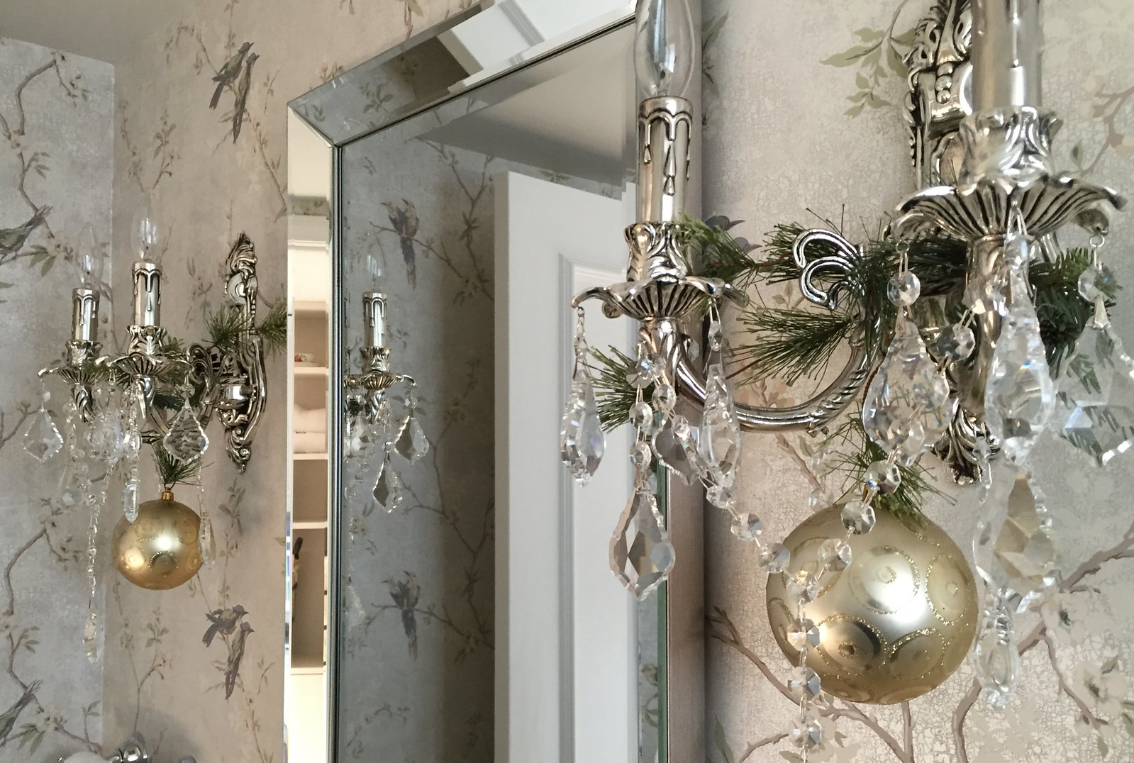 elegant powder room with evergreens and gold bauble on chandeliers