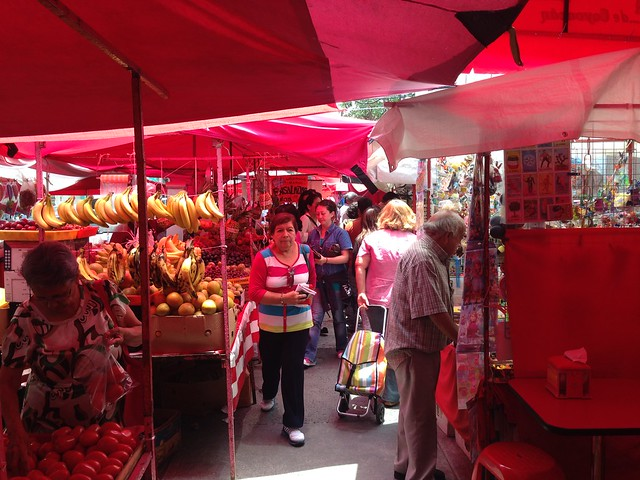 Neighbors walk through the narrow passageway between vendors
