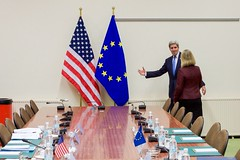 U.S Secretary of State John Kerry points the way before he and European Union High Representative for Foreign Affairs Federica Mogherini pose for photographers on December 1, 2015, at NATO Headquarters in Brussels, Belgium, before a bilateral meeting on the sidelines of a NATO Ministerial meeting. [State Department photo/ Public Domain]