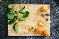 Apricots slices of apricot on a wooden board wiht…