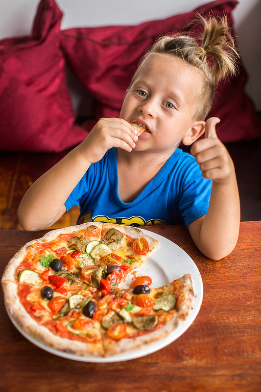 4 year old boy eating pizza in a restaurant