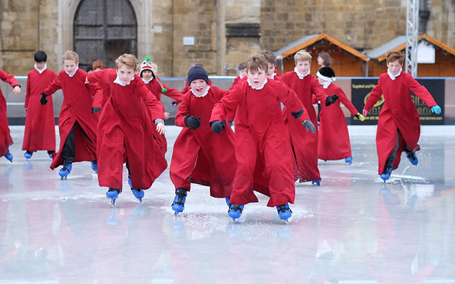 Choristers from Winchester Cathedral skate on the outdoor ice rink at Winchester Cathedral in Hampshire