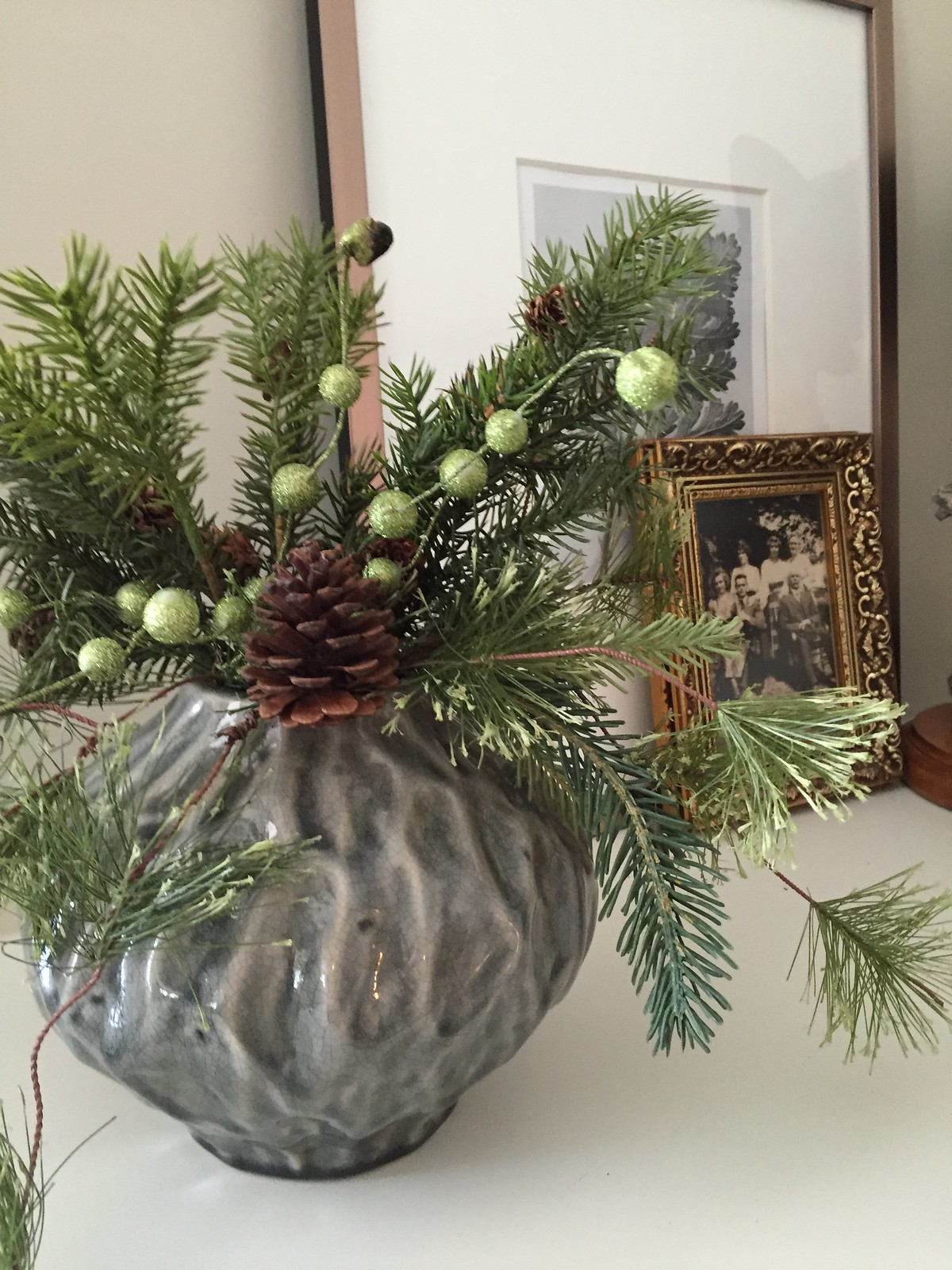 holiday decor with vase of evergreens on white shelf