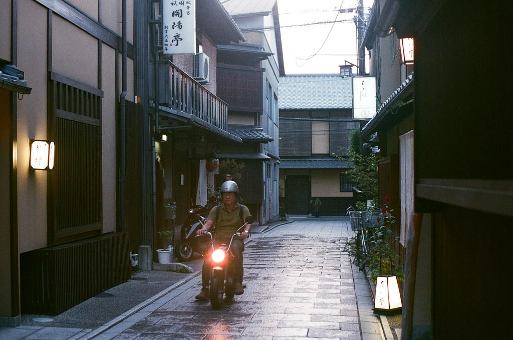 花見小路 巷弄 京都 Kyoto 2015/09/23 從清水寺下來後走進花見小路,那時候路上開始下雨,但我不愛撐傘,就只是把外套帽子戴上這樣,一路邊走邊拍。  看到有人騎小摩托車經過。  Nikon FM2 Nikon AI Nikkor 50mm f/1.4S AGFA VISTAPlus ISO400 0948-0036 Photo by Toomore