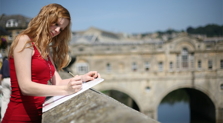 A student sketches at Pulteney Bridge in Bath