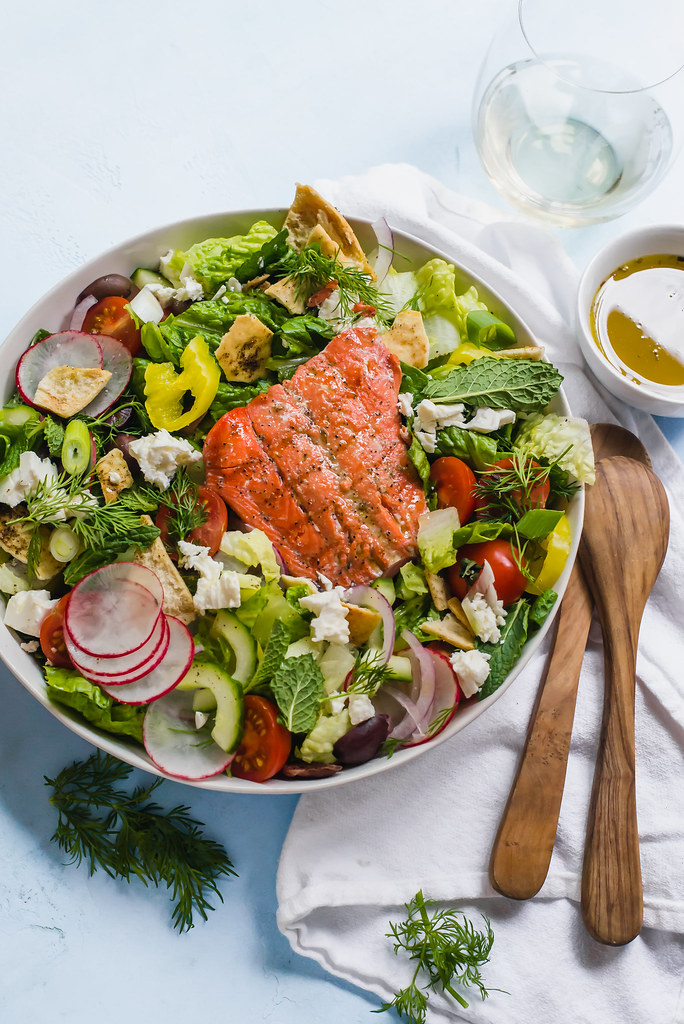 Loaded Greek Fattoush salad with grilled salmon, hearty vegetables and fresh herbs, creamy feta cheese and toasted pita chips. This is the ultimate Greek salad.