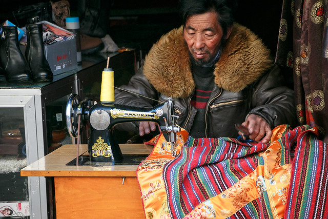 A man sewing Tibetan traditional clothes 店先でチベットの布を縫っている男性