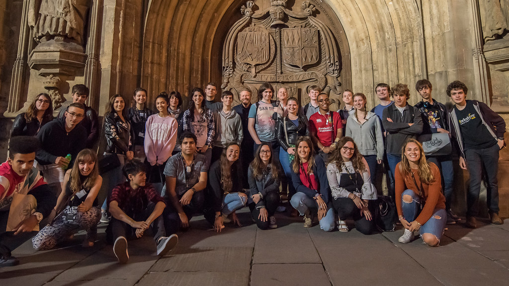 A group of students and helpers that attended the Autism Summer School posing for a photo outside Bath Abby
