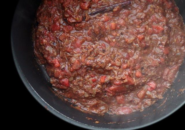 Uien, specerijen en tomaten basis voor curry