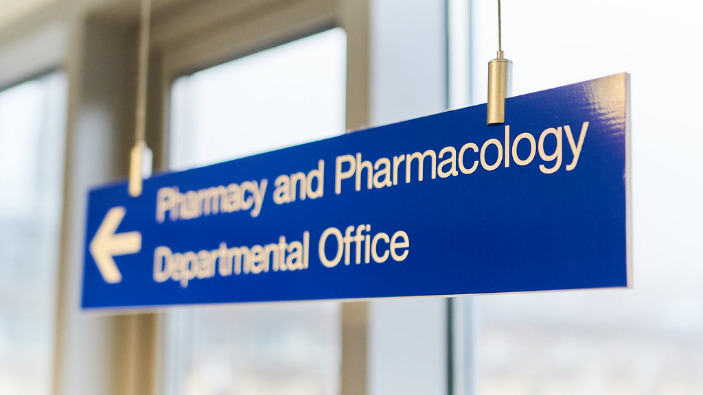 A sign pointing to the pharmcy and pharmacology offices