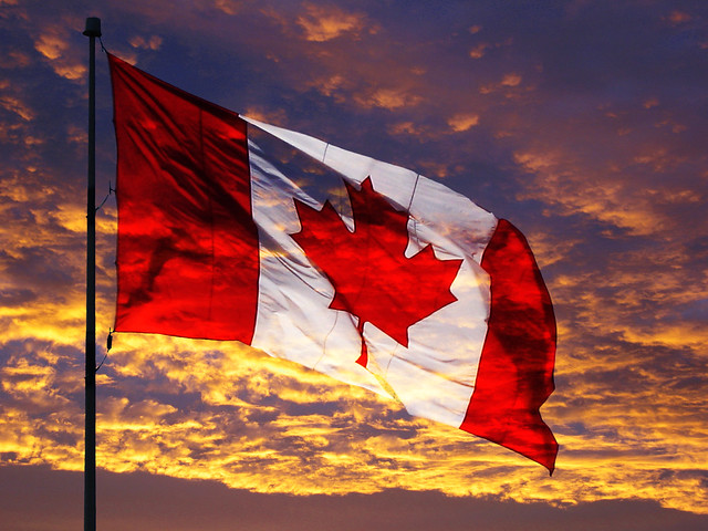Canadian flag flapping over a gold and purple sunset