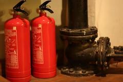 bottle(0.0), drink(0.0), lighting(0.0), alcoholic beverage(0.0), red(1.0), distilled beverage(1.0), fire extinguisher(1.0),