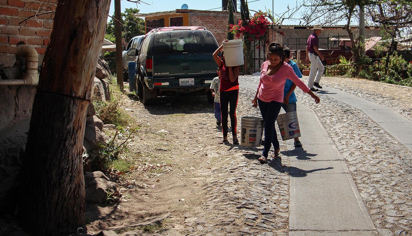 Niños llevan agua del Lago a sus casas