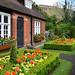 10. Casita junto a jardín repleto de flores con ventanas blancas de madera