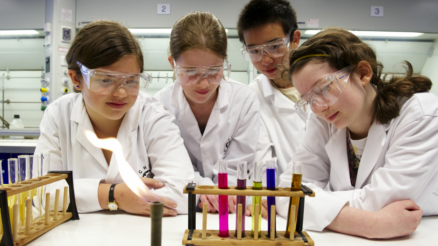 Four school children look at test tubes and a bunsen burner