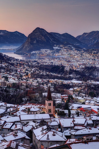 Panoramic view of Sonvico at sunrise, with Lugano city and lake in the background.