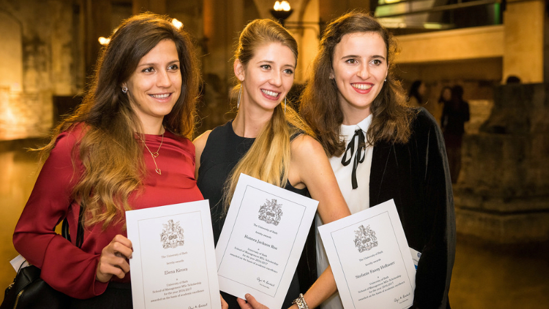 Three Gold Scholars pose with their degree certificates