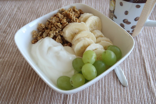 Knuspermüsli mit Bananenscheiben und Weintrauben auf Joghurt