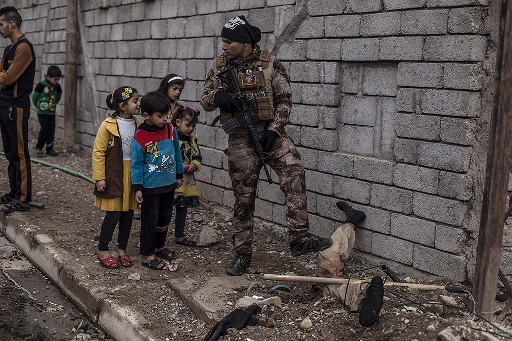 Iraqi children look at the body of a half buried Islamic State militant while talking to an Iraqi soldier which steps on the body of the militant in Al Barid district in Mosul, Iraq, 2016
