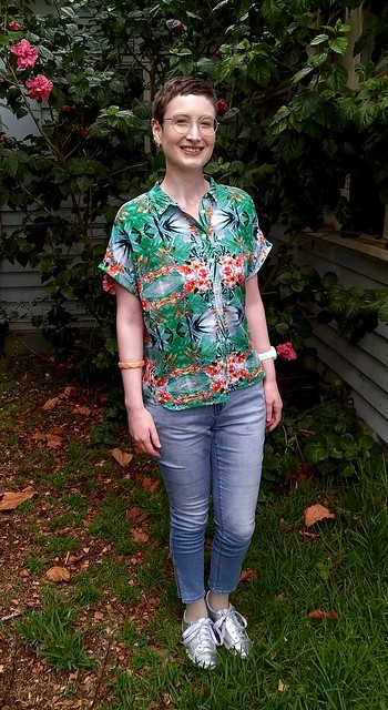 A woman stands in front of hibiscus plant. She wears a green, tropical print shirt, skinny jeans and silver runners.