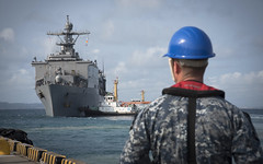 A Sailor looks on as USS Ashland (LSD 48) departs Okinawa, March 19. (U.S Navy/MC2 Sarah Villegas)